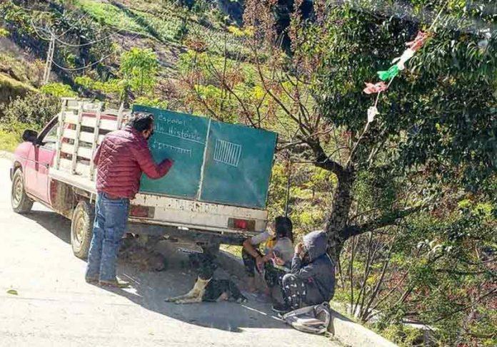 Professor pendura lousa em caminhão e dá aulas em área rural